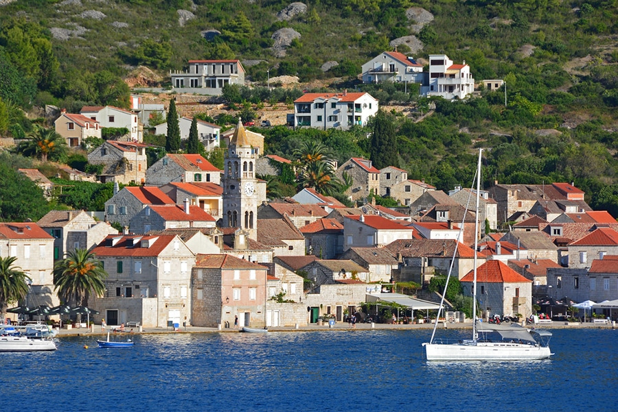 a traditional built and modern architecture along with boats sailing the coasts of Vis island in Croatia