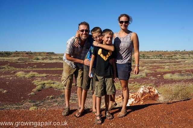a family posing in front of a valley growing a pair