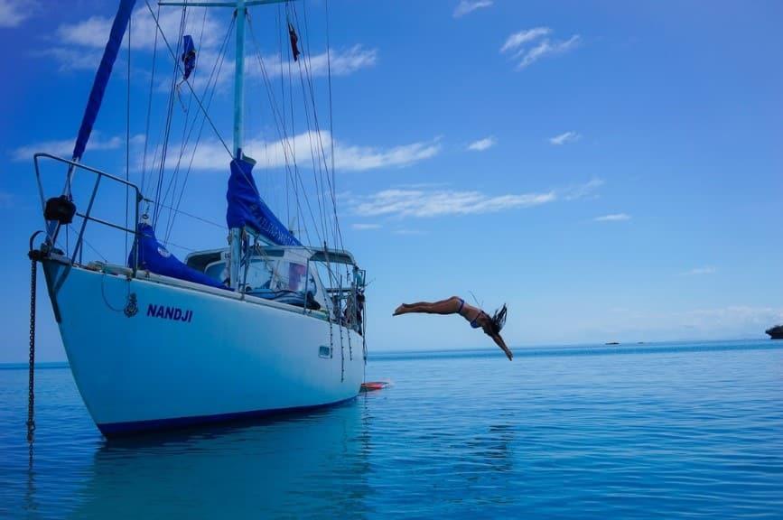 a girl jumping off a sailing nanji boat