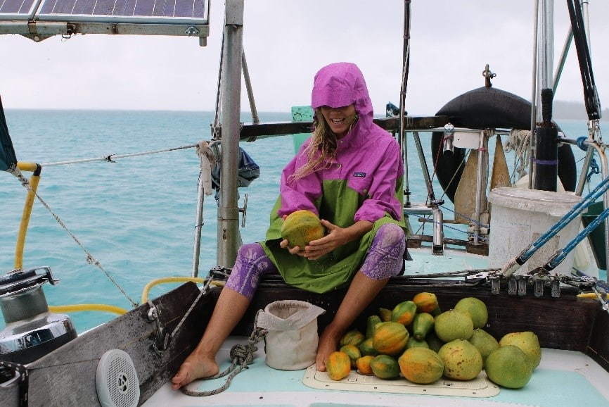 a woman representing swell voyage sailing blog sitting on a boat with a mellon