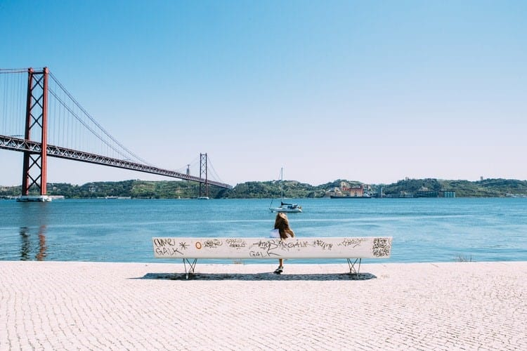 a girl sitting on bench looking at sail boats in the San Francisco Bay area