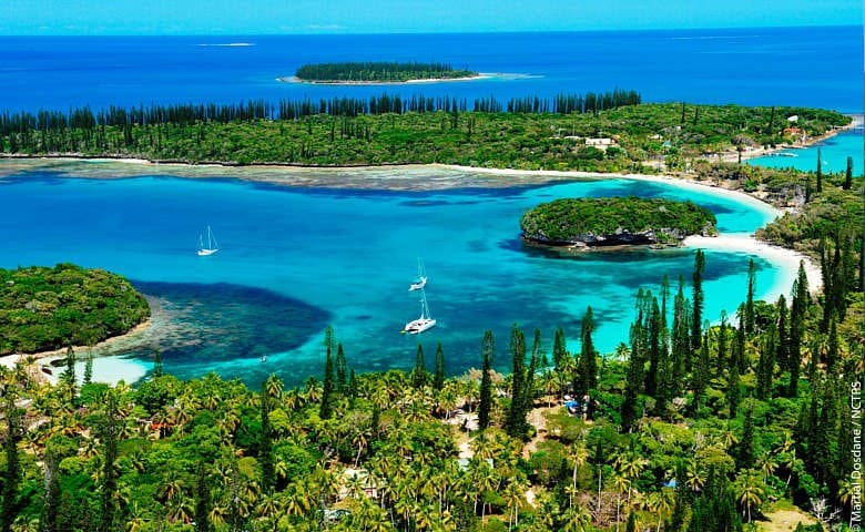 boats sailing in the blue lagoon of The Island of Pines New Caledonia